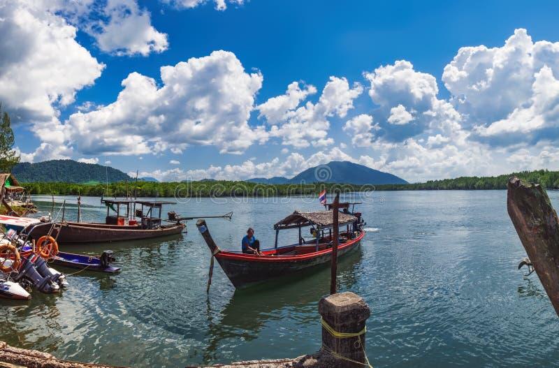 有泰国妇女的小渔船靠码头对码头 库存照片