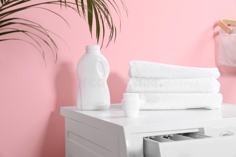 有洗涤剂和清洁毛巾的瓶在洗衣机 免版税库存照片