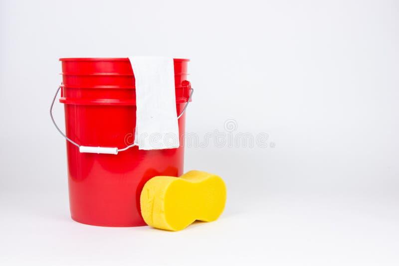 有洗涤布料的红色在白色背景的桶和海绵 免版税库存图片