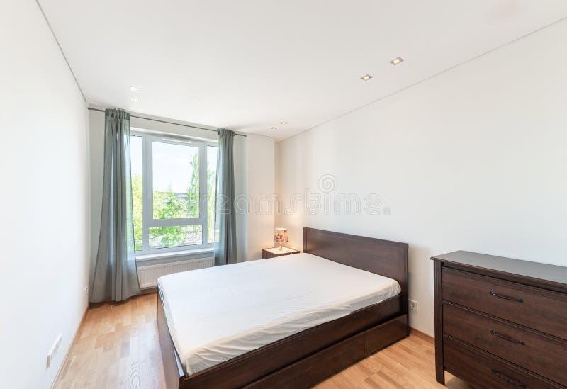 有洗脸台、胸口和窗口的卧室 明亮的白色墙壁 图库摄影