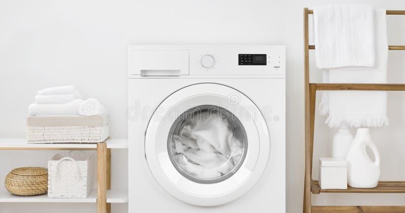 有洗衣店的在白色墙壁背景的洗衣机和架子 图库摄影