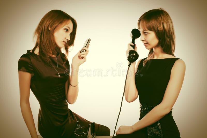有流动和减速火箭的电话的两名愉快的年轻时尚妇女 免版税库存图片