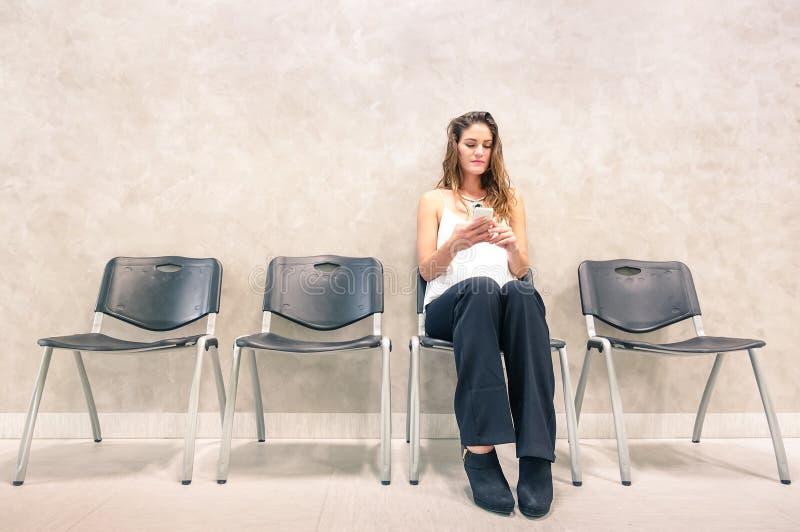 有流动巧妙的电话的沉思少妇在候诊室 免版税库存照片