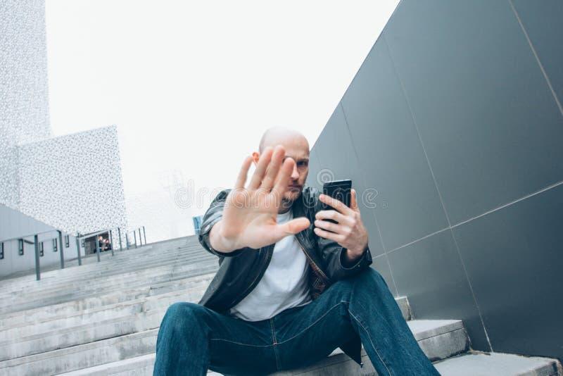 有流动开会的成人秃头有胡子的严肃的人在台阶用手结束照相机,没有照片 免版税库存图片