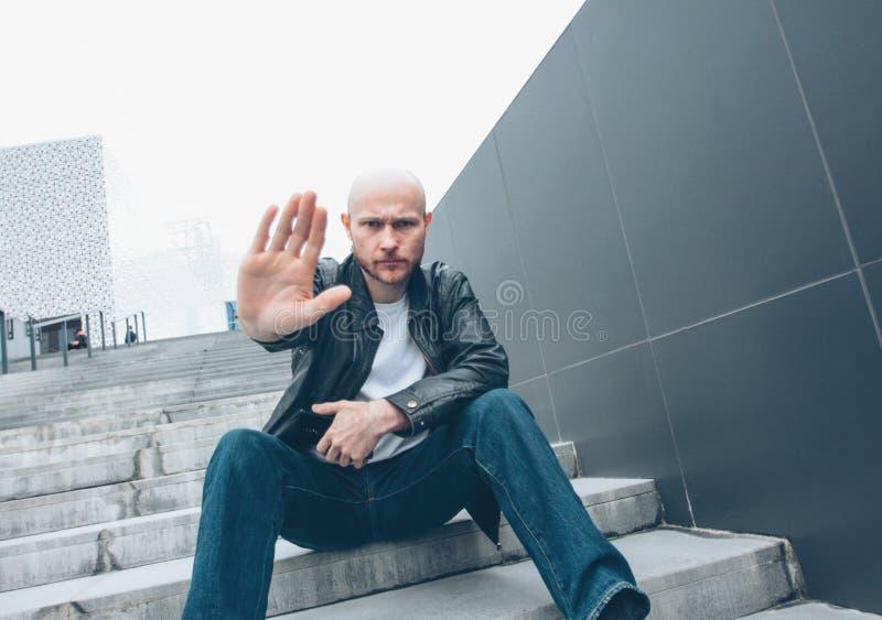 有流动开会的成人秃头有胡子的严肃的人在台阶用手结束照相机,没有照片 免版税图库摄影