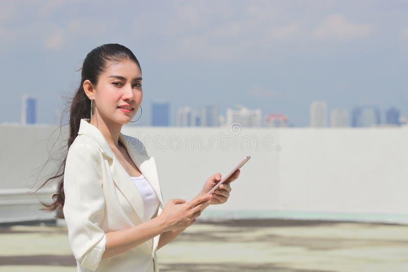 有流动智能手机的确信的年轻亚裔妇女购物的网上身分的户外 免版税图库摄影