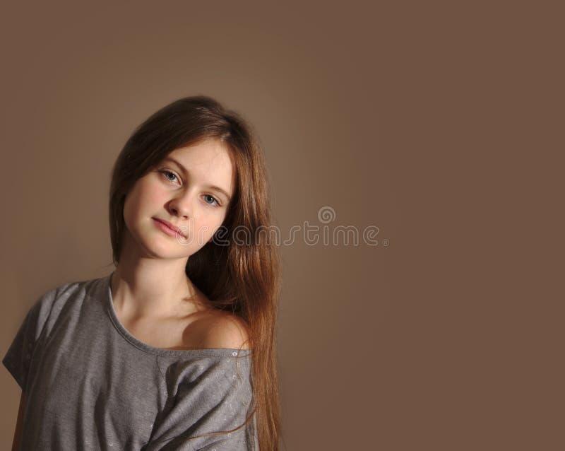 有流动的头发的蓝眼睛的棕色毛发的害羞的女孩 库存图片