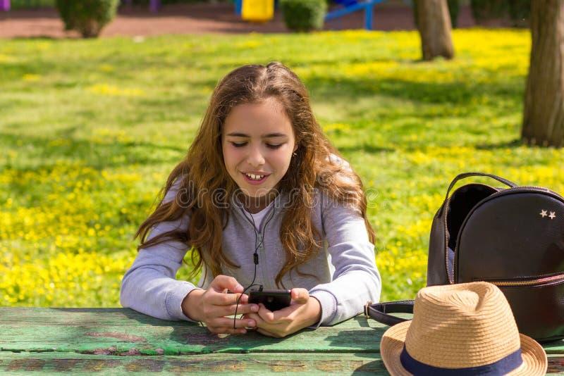 有流动cellpfone智能手机的俏丽的少年女孩在夏天公园 库存照片