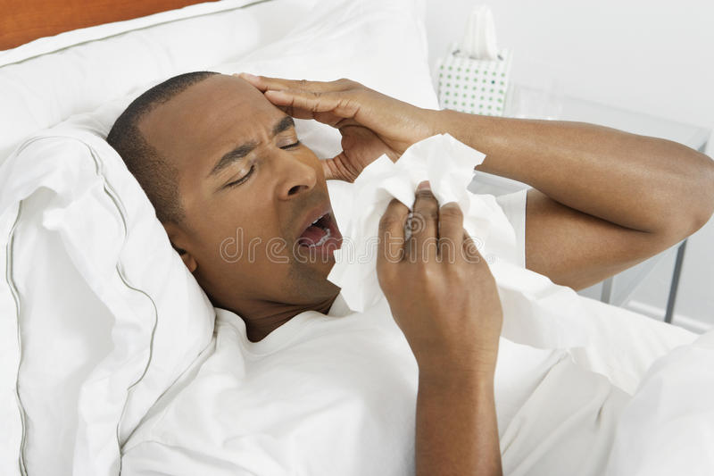 有流感的人在床上 免版税库存图片