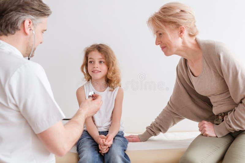 有流感的小男孩在有他爱恋的母亲的儿科医生的办公室 免版税图库摄影