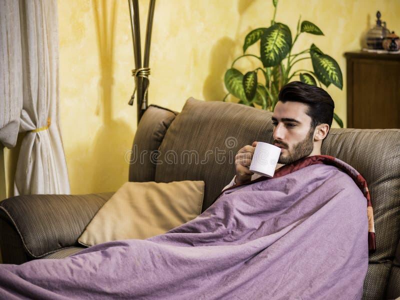 有流感的年轻人病残喝清凉茶的 免版税库存照片