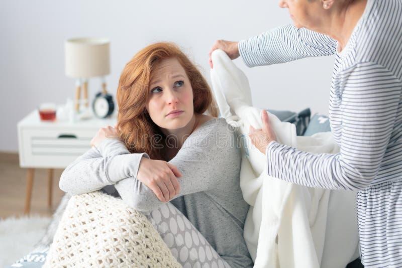 有流感的母亲支持的女儿 免版税库存图片