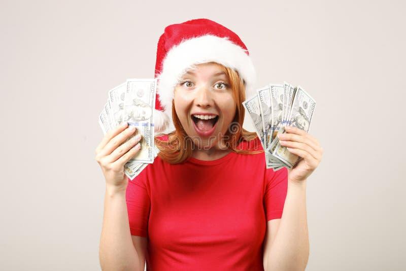 有流行音乐pom的逗人喜爱的红发女性佩带的圣诞老人` s帽子,庆祝冬天欢乐季节假日 免版税库存照片