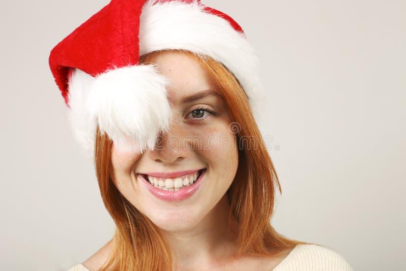 有流行音乐pom的逗人喜爱的红发女性佩带的圣诞老人` s帽子,庆祝冬天欢乐季节假日 免版税图库摄影