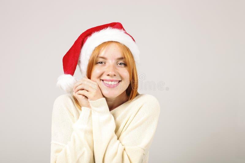 有流行音乐pom的逗人喜爱的红发女性佩带的圣诞老人` s帽子,庆祝冬天欢乐季节假日 库存图片
