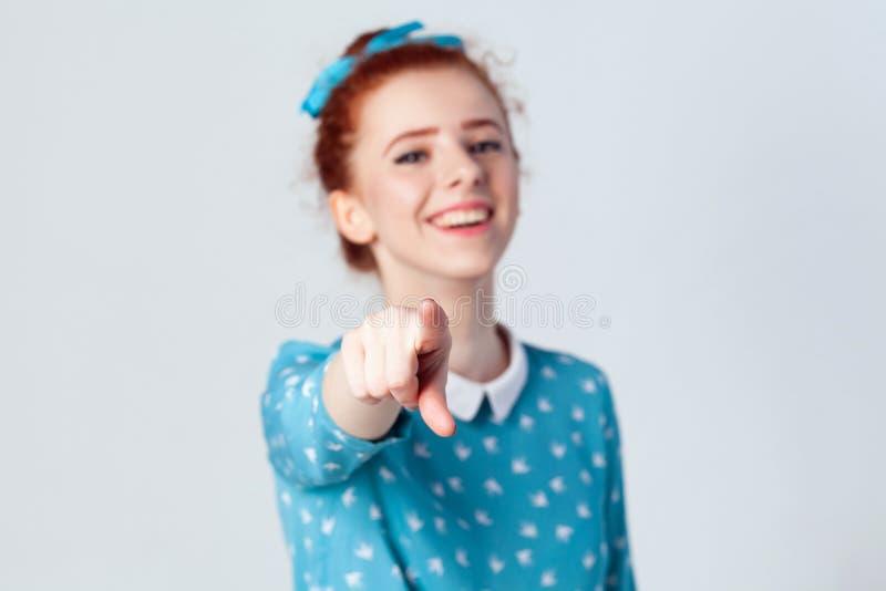 有浅兰的礼服的滑稽的姜女孩,把手指指向照相机和暴牙的微笑,在她的手指的焦点 免版税库存图片