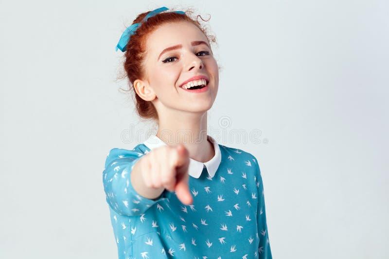 有浅兰的礼服的滑稽的红头发人女孩,把手指指向照相机和暴牙的微笑,在她的面孔的焦点 库存照片