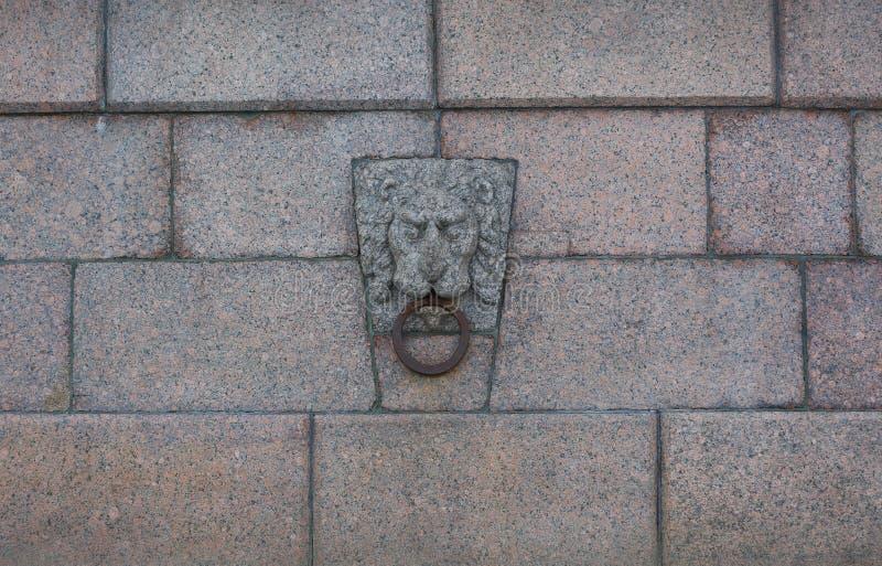 有浅浮雕的花岗岩墙壁以有一个圆环的狮子的头的形式在它的嘴 免版税库存图片