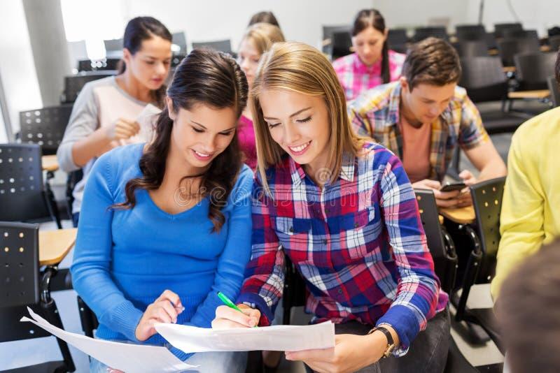 有测试的愉快的学生女孩在教室 库存照片