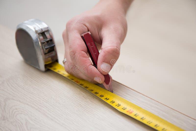 有测量的磁带和新的被碾压的木地板的男性手 库存图片
