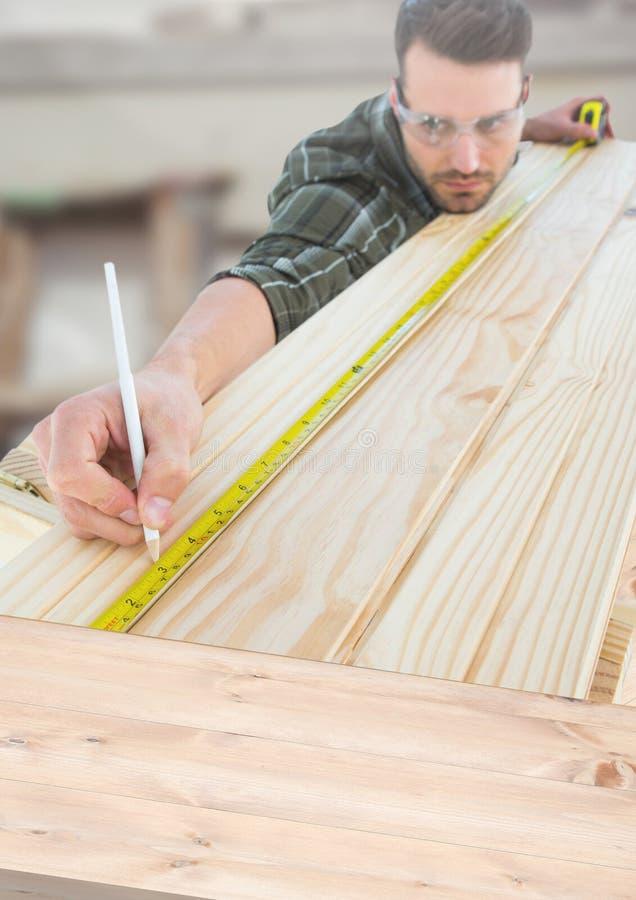 有测量的磁带的木匠在建筑工地 皇族释放例证