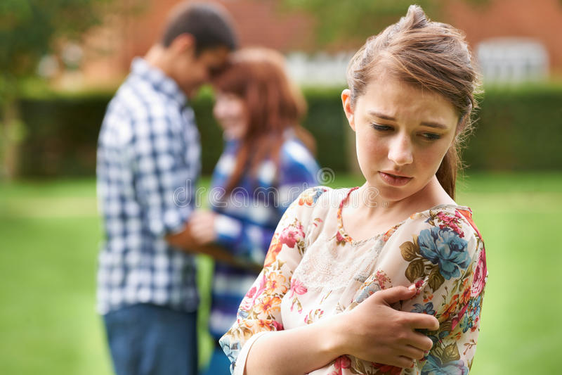 有浪漫夫妇的孤独的嫉妒的十几岁的女孩在背景中 图库摄影
