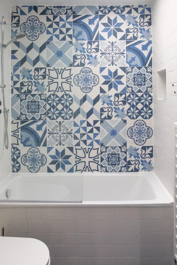 有浴的,洗手间,在墙壁和水池单位的适当位置卫生间,与在浴上的蓝色和白色补缀品瓦片 库存图片