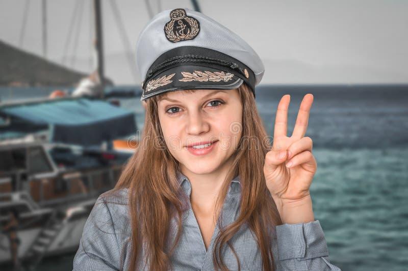 有海员帽陈列胜利标志的愉快的女性上尉 免版税库存照片