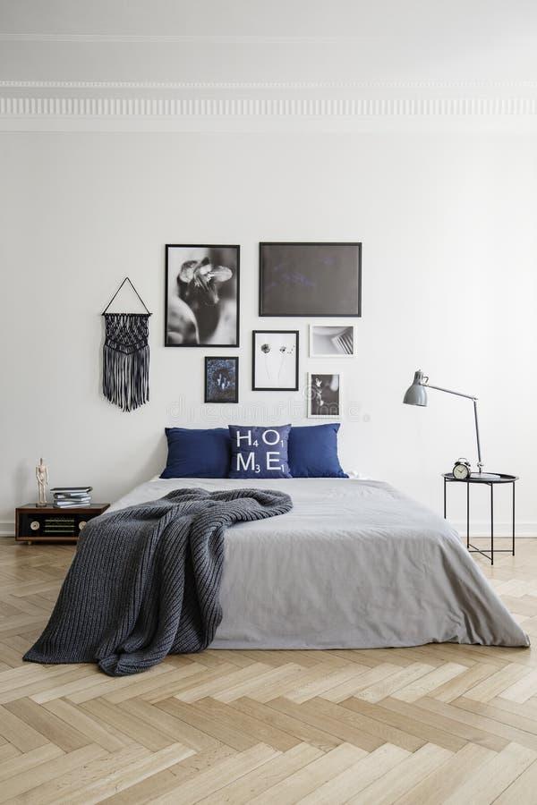 有海报画廊的蓝色和灰色卧室在时髦的内部的 免版税库存图片