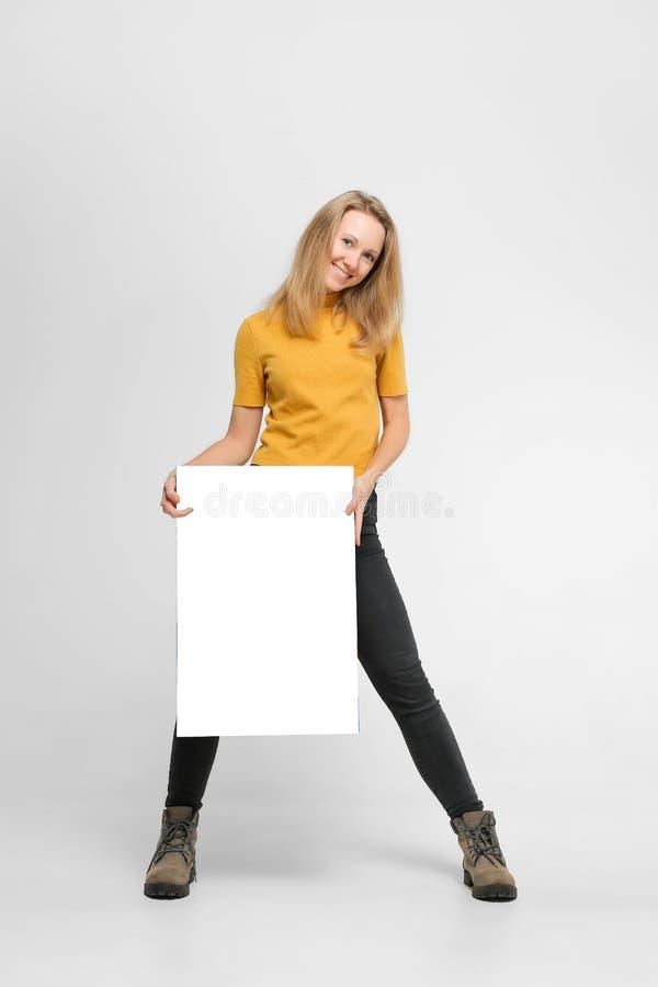 有海报的微笑的年轻女人 免版税图库摄影