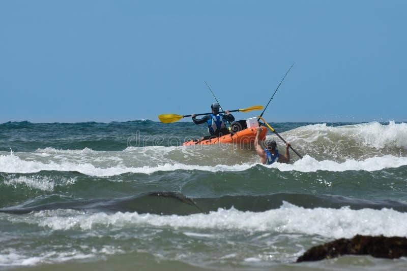 有海洋皮船的渔夫在波浪 免版税图库摄影
