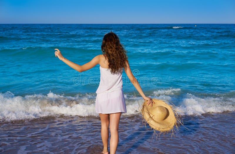 有海滩帽子的女孩在海在夏天 免版税库存图片