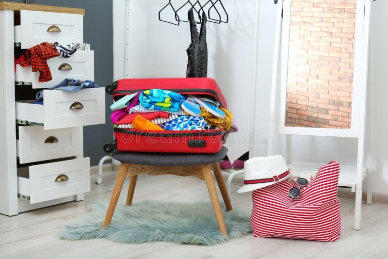 有海滩衣裳和辅助部件的手提箱在凳子在化装室 免版税图库摄影