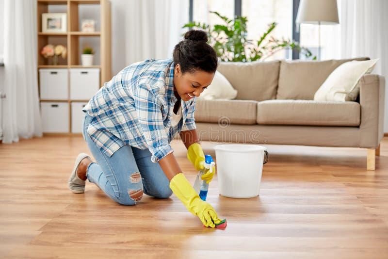 有海绵清洁地板的非洲妇女在家 免版税图库摄影