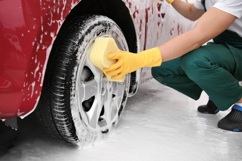 有海绵的男性工作者清洁车轮子在汽车 免版税库存图片
