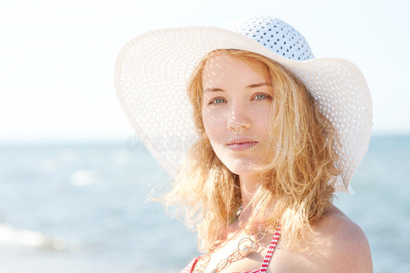 有海滩帽子的美丽的年轻白肤金发的妇女 免版税库存照片