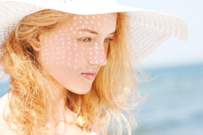 有海滩帽子的美丽的年轻白肤金发的妇女 库存图片
