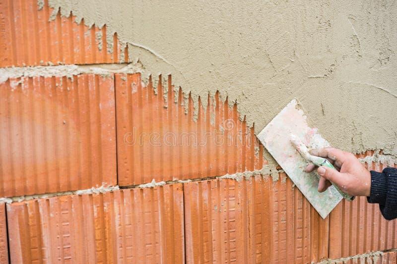 有涂灰泥墙壁的修平刀的男性石膏工胳膊在工地工作 库存照片
