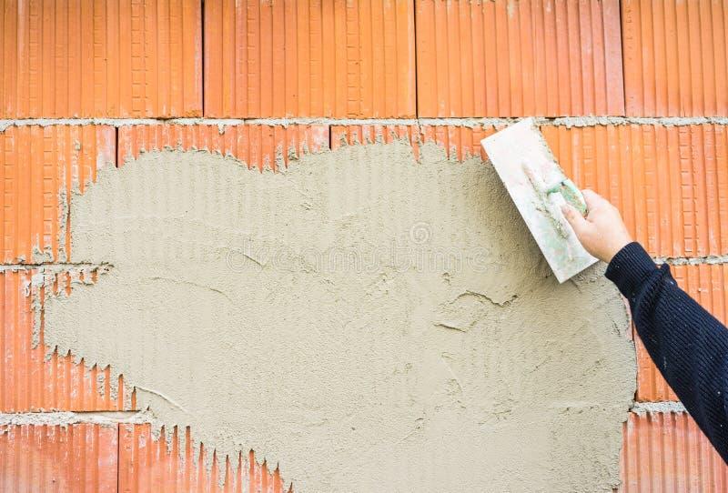 有涂灰泥砖墙的修平刀的男性工作者胳膊 库存图片
