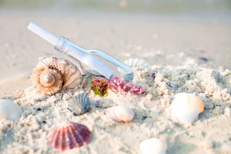 有消息的在海滩的瓶或信件在贝壳附近 sos 复制空间 库存图片