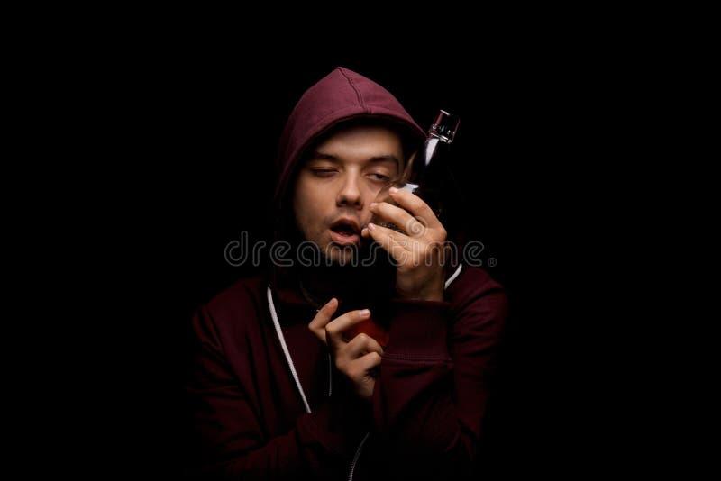 有消沉的一个残破和孤独的醺酒的人在黑背景 与瓶的一个男性有很多酒精饮料 免版税库存照片