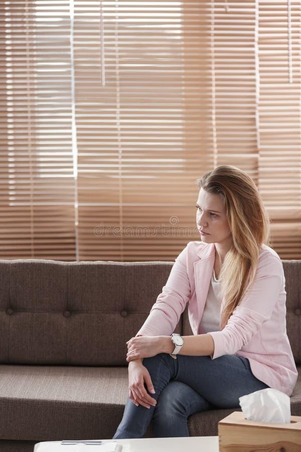 有消沉的少妇单独坐有的一个长沙发tiss 免版税库存图片