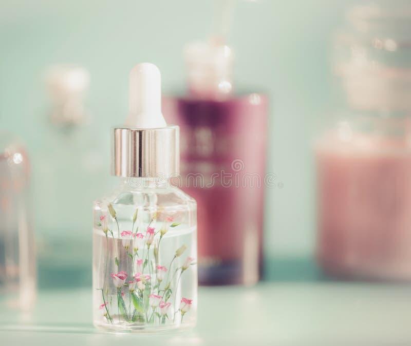 有液体、吸移管和小的桃红色花的透明化妆瓶 花卉精华或草本萃取物血清在桌,前面v上 免版税库存照片