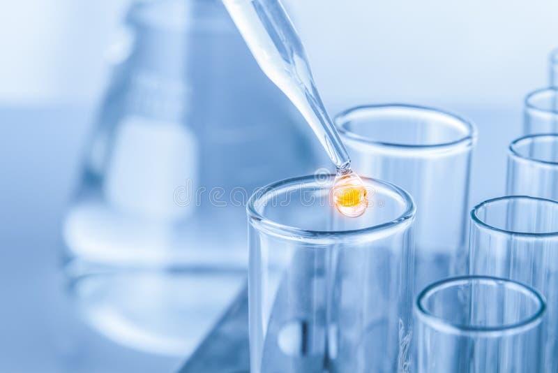 有液体滴的实验室吸移管在玻璃试管的 免版税图库摄影