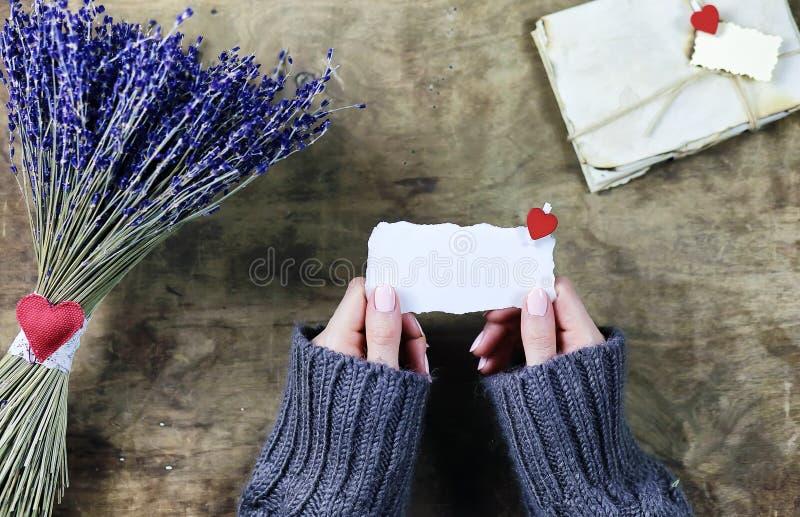 有淡紫色花束的女孩在木桌上开花 免版税库存图片