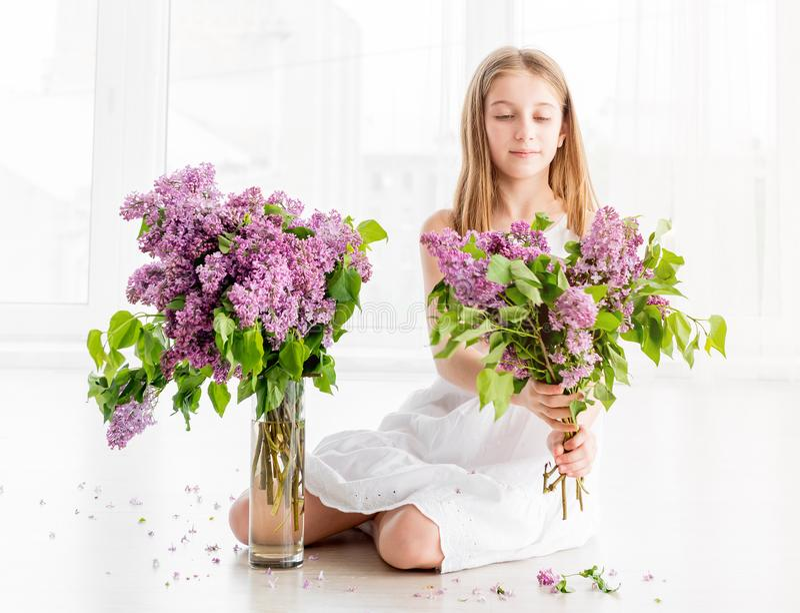 有淡紫色花花束的女孩坐地板 图库摄影