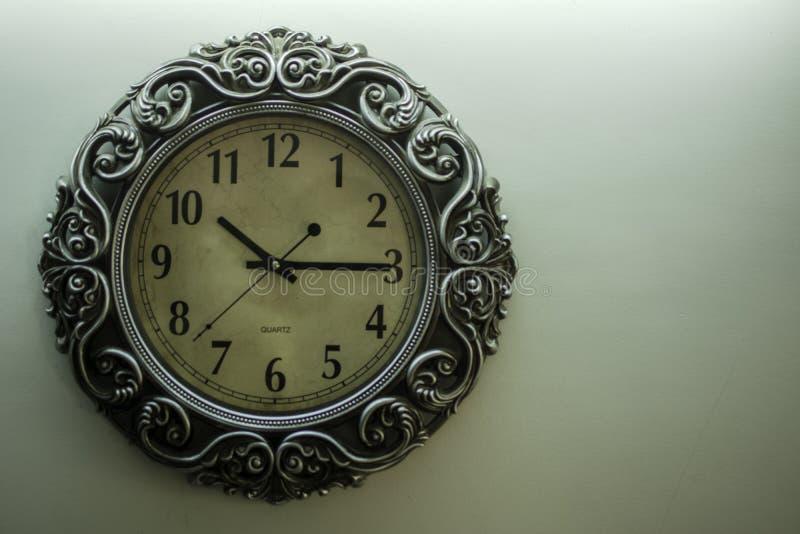 有淡黄色后面地面陈列时间10:15时的古老设计师壁钟和在右边的自由spac 免版税库存照片