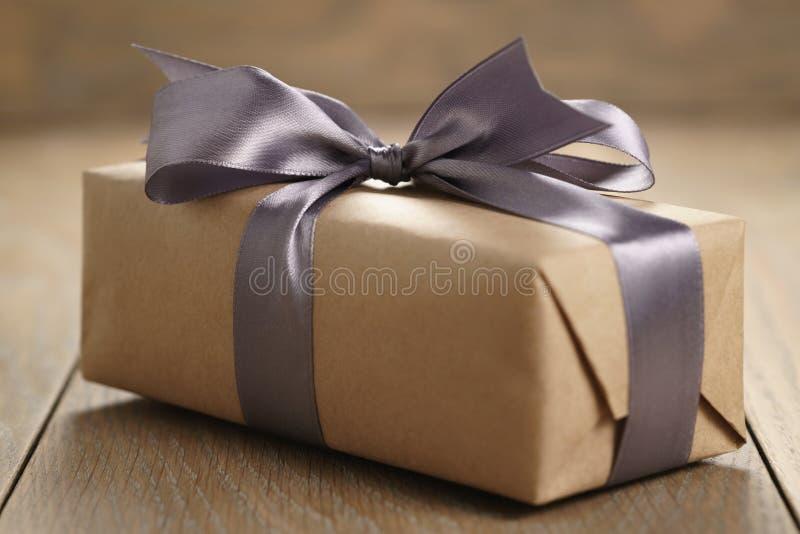 有淡紫色丝带弓的土气工艺纸礼物盒在木桌上 库存照片