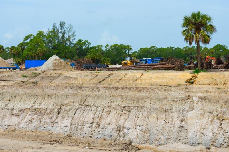 有深坑挖掘和工作卡车的建造场所 库存照片