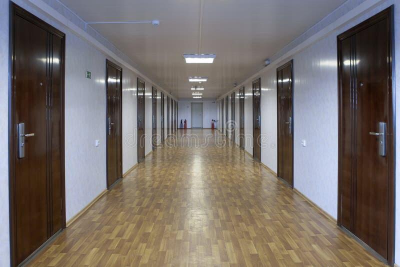 有深红木头的许多门的长的办公室走廊 库存图片